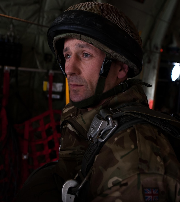 A U.K. Royal Army soldier looks out the back of a C-130J Super Hercules as he and his unit prepare to jump out of it during an International Jump Week exercise over Germany Dec. 1, 2016. Approximately a dozen NATO allies sent troops to participate in the exercise. (U.S. Air Force photo by Airman 1st Class Lane T. Plummer)