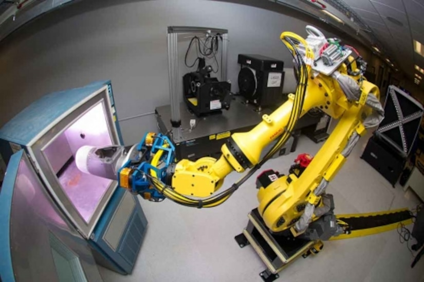 A robotic arm places a small-diameter bomb II guidance section into a test cell. Courtesy photo