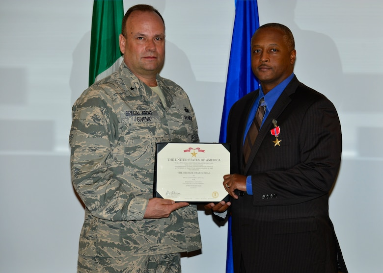 Brig. Gen. Keith Givens, Air Force Office of Special Investigations commander, presents the Bronze Star Medal certificate to Special Agent Robert Binns, AFOSI Detachment 531 superintendent, at Aviano Air Base, Italy on Dec. 5, 2016. Binns earned the medal by distinguishing himself by meritorious achievement while engaged in operations against an opposing force in Afghanistan from Dec. 7, 2012 to Dec. 10, 2013. (U.S. Air Force photo by Senior Airman Cary Smith)