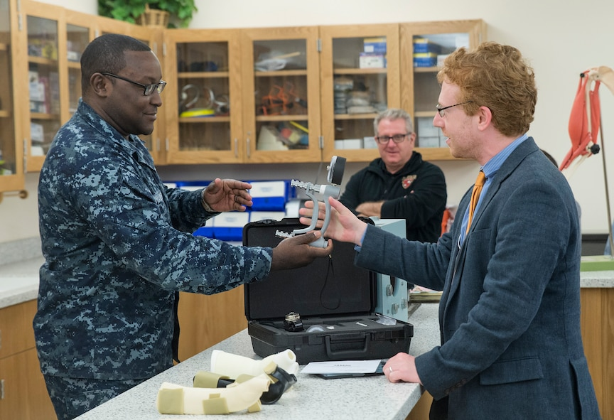 Petty Officer 1st Class Derrick Charles, Naval Training Support Center instructor, tests the grip strength of Johnathan Cristol, World Policy Institute fellow, during an occupational therapy demonstration at the Medical Education and Training Campus Nov. 30, 2016 at Joint Base San Antonio-Ft. Sam Houston, Texas. The civic leaders also toured a C-5M Super Galaxy aircraft, the Medical Training and Education Campus at Joint Base San Antonio-Ft. Sam Houston, and the Center for the Intrepid. (U.S. Air Force photo by Benjamin Faske)