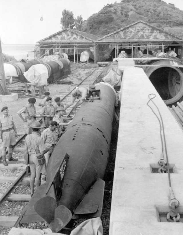 Sometime just after the end of World War II, Allied forces prepare to transport a Japanese mini-submarine on rail tracks from the warehouse to the dockside in Yokosuka, Japan.