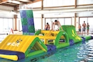 Nine-year-old Owen Gray, left, son of Lt. Col. Peter Gray, a professor of military science at Kansas State University, races against his brother Jackson across an inflatable obstacle course Nov. 5 during Wibit Family Fun Day at Eyster Pool. The family fun day is a day of recreation swim and play with an inflatable obstacle course, a rock wall and children's water slide.
