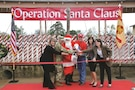 LEFT TO RIGHT: Christine Benne, Association of the United States Army representative; Col. John D. Lawrence, Fort Riley garrison commander; Santa Claus; Master Sgt. Michael Ewing, head elf at Santa's Workshop; LeAnn Martin, wife of Maj. Gen. Joseph Martin, 1st Infantry Division and Fort Riley commanding general; and Alissa Turner, wife of Brig. Gen. William A. Turner, 1st Infantry Division deputy commanding general, cut the ribbon Nov. 2 at Santa's Workshop, 261 Stuart Ave, signifying the beginning of the Christmas season for Operation Santa Claus. For 32 years, Operation Santa Claus has provided military children from birth to 18 with presents to open on Christmas morning.
