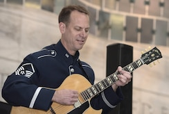 Master Sgt. Geoffrey Reecer, U.S. Air Force Band's Airmen of Note guitarist, performs at the National Museum of American History in Washington, D.C., Dec. 3, 2016. The group played holiday favorites throughout the afternoon for museum visitors to spread cheer during the season. (U.S. Air Force photo by Senior Airman Jordyn Fetter)