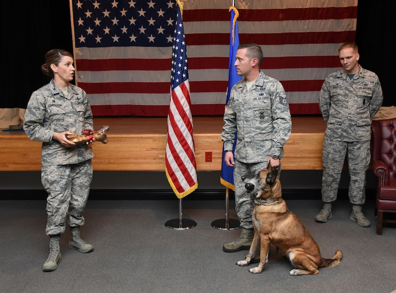 Col. Michele Edmondson, 81st Training Wing commander, delivers remarks to Tech. Sgt. James Martin III, 81st Security Forces Squadron charlie flight flight chief, and Densy, 81st SFS military working dog, during Densy's retirement ceremony at the Keesler Medical Center Don Wylie Auditorium Dec. 2, 2016, on Keesler Air Force Base, Miss. Densy served more than nine years in the Air Force. After serving together for two years, to include one deployment, Martin adopted Densy. (U.S. Air Force photo by Kemberly Groue)