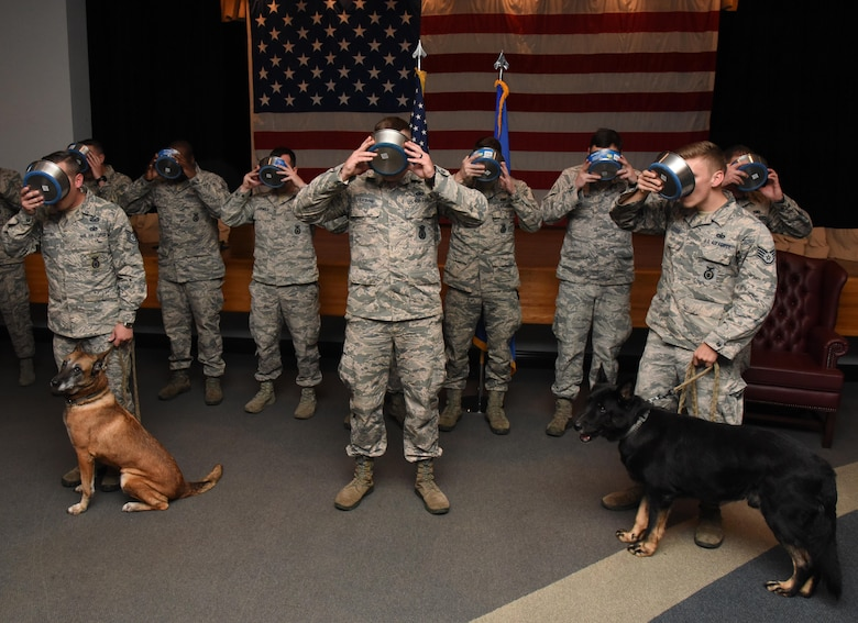 Members of the 81st Security Forces Squadron drink a toast from dog food bowls to Densy and Ares, 81st SFS military working dogs, during their retirement ceremony at the Keesler Medical Center Don Wylie Auditorium Dec. 2, 2016, on Keesler Air Force Base, Miss. They served more than 17 years combined in the Air Force. (U.S. Air Force photo by Kemberly Groue)