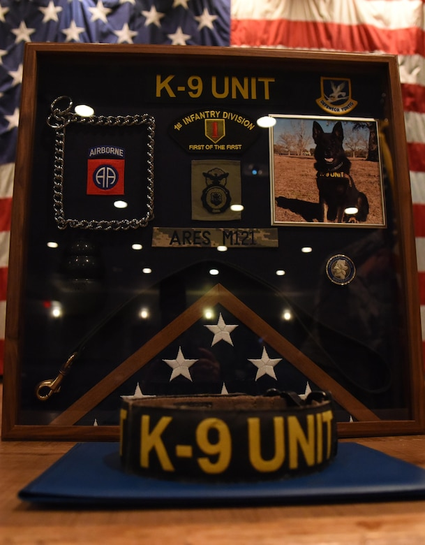 A shadowbox for Ares, 81st Security Forces Squadron military working dog, sits on display during his retirement ceremony at the Keesler Medical Center Don Wylie Auditorium Dec. 2, 2016, on Keesler Air Force Base, Miss. He served more than eight years in the Air Force. After serving together for two years, to include one deployment, Staff Sgt. Jordan Leiter, 81st SFS military working dog handler, adopted Ares. (U.S. Air Force photo by Kemberly Groue)