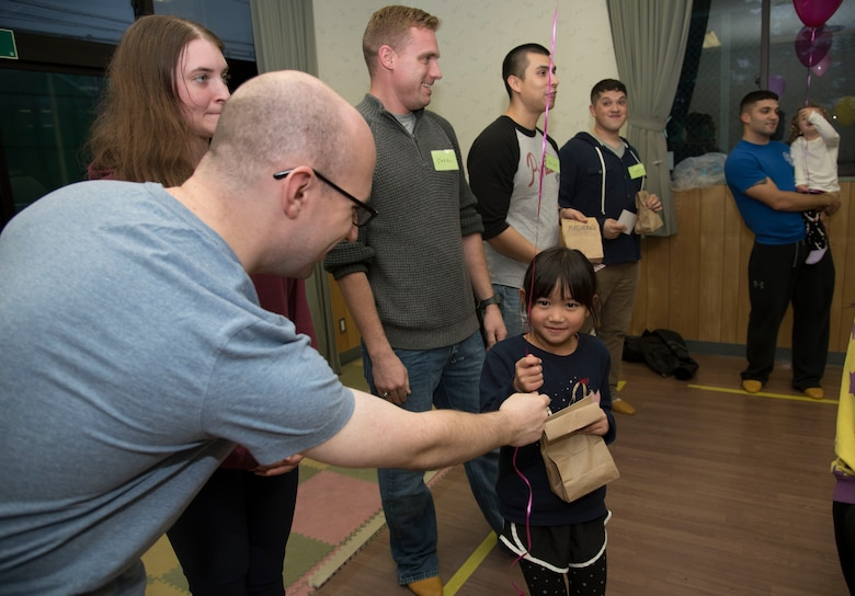 U.S. Air Force Airman 1st Class Ryan Friel, a 35th Communications Squadron cyber transport technician, hands a balloon to a Japanese national during a Jido-kan class at Okamisawa Grade School, Misawa City, Japan, Nov. 22, 2016. During the class, Airmen go over songs, reading and studying flashcards in English with the grade schoolers. (U.S. Air Force photo by Airman 1st Class Sadie Colbert)