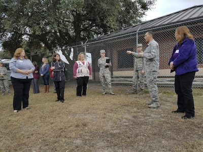 Joint Base Charleston spouses listen to Tech. Sgt. Jonathan Calo, 628th Security Forces Squadron military working dog trainer, right, as they participate in a base tour of Joint Base Charleston, S.C., Dec. 5, 2016. Spouses had the opportunity to tour various mission sets across the Air Base.