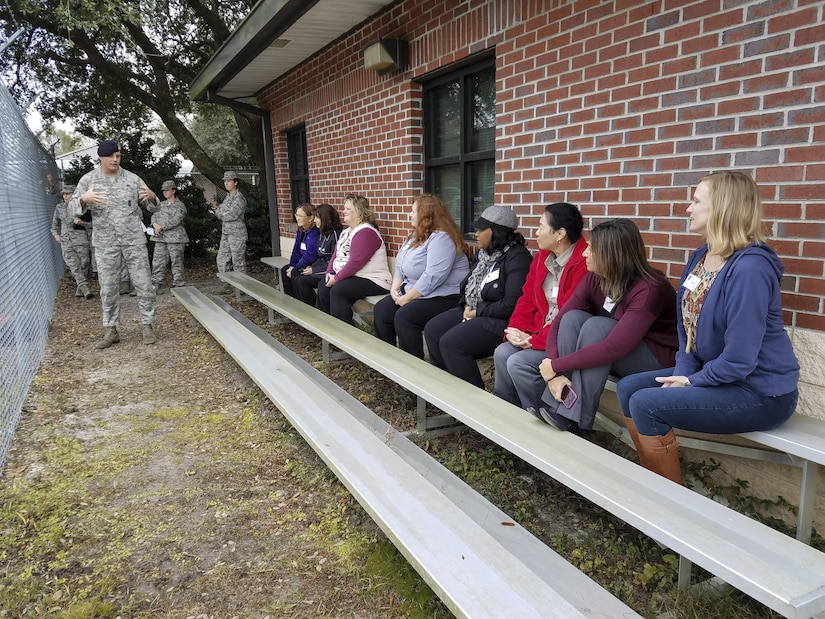 Tech. Sgt. Timothy Garrett, 628th Security Forces military working dog kennel master, left, explained the training process for the dogs to Joint Base Charleston spouses during a tour here Dec. 5, 2016. The spouses had the opportunity to visit several tour stops across the Air Base and learn about various mission sets.