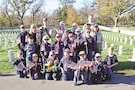 Cub Scouts and leaders of Pack 260 of Fort Riley place American flags in front of tombstones in the Post Cemetery Nov. 10 in honor of Veterans Day.