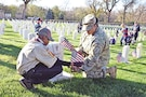 Staff Sgt. Tara Flournoy, 101st Brigade Support Battalion, 1st Armored Brigade Combat Team, 1st Infantry Division, and her son, Jaheim, a Webelo with Cub Scout Pack 260, place an American flag in front of a tombstone in the Post Cemetery Nov. 10 in honor of Veterans Day.
