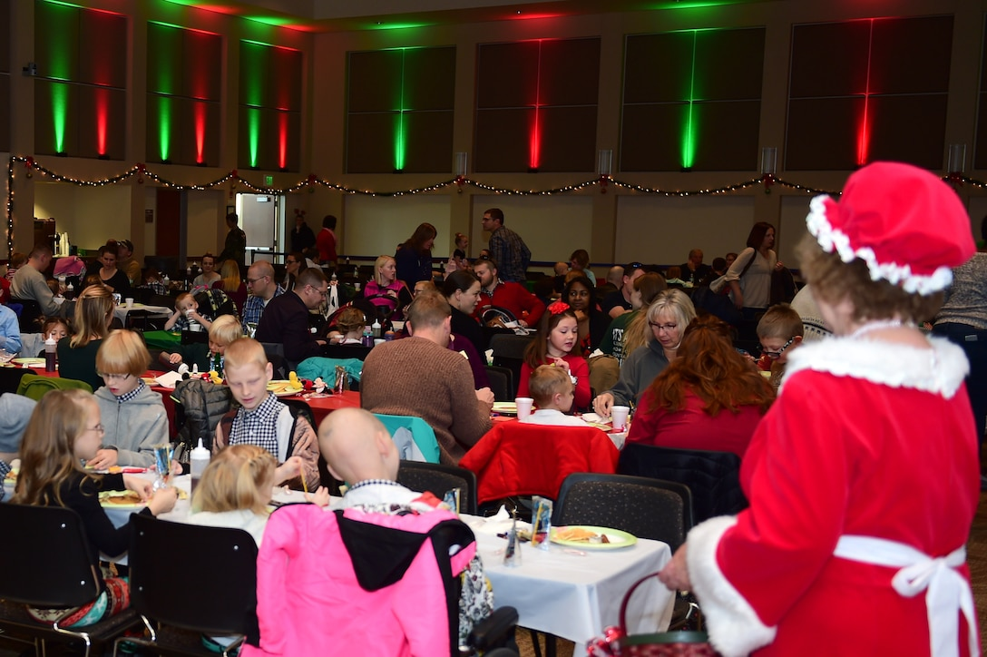 Mrs. Claus watches over the participants as they eat at a Breakfast with Santa event Dec. 3, 2016, on Buckley Air Force Base, Colo. Claus spent the morning greeting children and handing out candy canes. (U.S. Air Force photo by Airman Jacob Deatherage/Released)