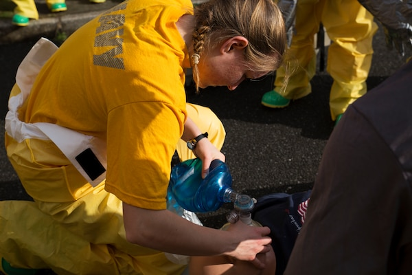 U.S. Navy Seaman Rebecca Mann, a member of the hazardous material team with the Robert M. Casey Medical and Dental Clinic, supplies air to her mock patient at Marine Corps Air Station, Japan, Dec. 1, 2016. The clinic holds decontamination training biannually to prepare the base for real-world chemical contaminations. (U.S. Marine photo by Lance Cpl. Gabriela Garcia-Herrera)
