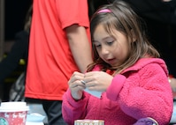 Miyah Riggs, 7, daughter of Tech. Sgt. Justin Riggs, 61st Aircraft Maintenance Unit F-35 expeditor, makes holiday gifts during Holiday Magic Dec. 3, 2016 at Luke Air Force Base, Ariz. The event featured rock climbing, bouncy houses, and vouchers for free Christmas trees to Luke community members. (U.S. Air Force photo by Airman First Class Alexander Cook)