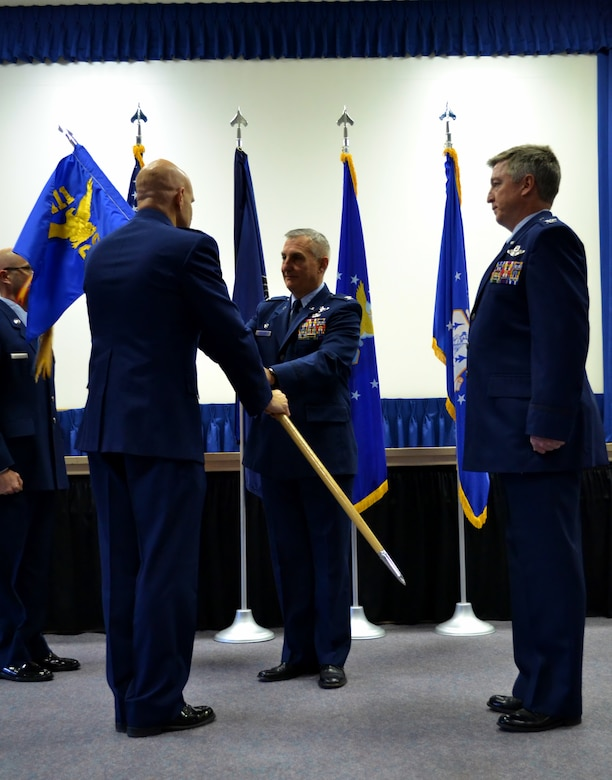 Col. Howard Eissler, the 111th Attack Wing commander, hands the 111th Operations Group guidon to former 111th OG Commander retired Col. Michael Shenk as the incoming operations group commander, Col. John O'Brien, stands awaiting the ceremonial transfer of position during the 111th OG Change of Command Ceremony conducted at the 111th Attack Wing headquarters, Horsham Air Guard Station, Pa., Dec. 3, 2016. The transition postured O'Brien as the highest ranking official for the unit's remotely-piloted aircraft mission. (U.S. Air National Guard photo by Tech. Sgt. Andria Allmond)