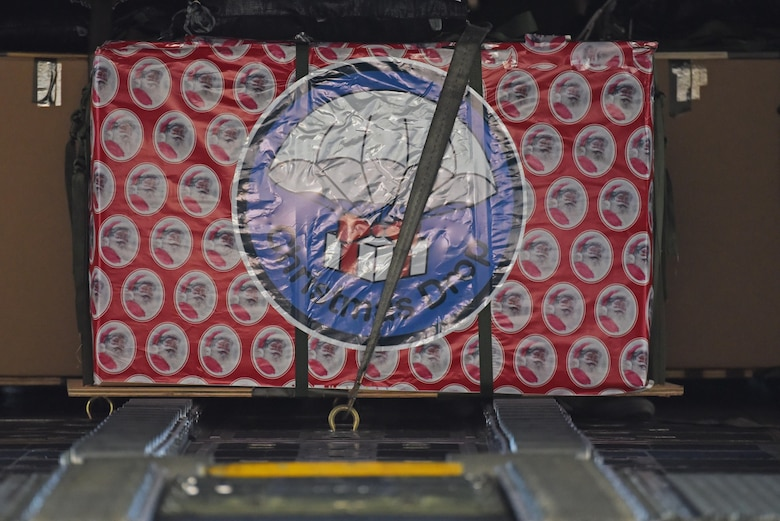 A wrapped Christmas box sits in a C-130 Hercules Dec. 6, 2016, at Andersen Air Force Base, Guam. This year marks 65 years of Operation Christmas Drop which provides joint airlift training opportunities for both peace and wartime efforts.(U.S. Air Force Photo by Airman 1st Class Jacob Skovo)