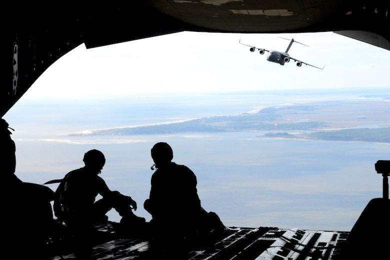 Staff Sgt. Jeffrey Michal, left, and Master Sgt. Gregory Long, right, 14th Airlift Squadron loadmasters, enjoy the view during a Key Spouse orientation flight heading to Northfield Auxiliary Airfield, S.C., Mar. 5, 2016. The C-17 Globemaster III has been stationed at Joint Base Charleston since 1993.