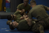 U.S. Marines with the Provost Marshal's Office are tased to demonstrate a daisy-chain take down during Taser Certification Training at Marine Corps Air Station Iwakuni, Japan, Nov. 31, 2016. Individual prongs from the X26 Taser were fired at the two Marines before simulating a fight where touching each other completed the electrical circuit causing neuromuscular incapacitation. Neuromuscular incapacitation causes the subject's muscles contract and lock up, making the individual unable to move.