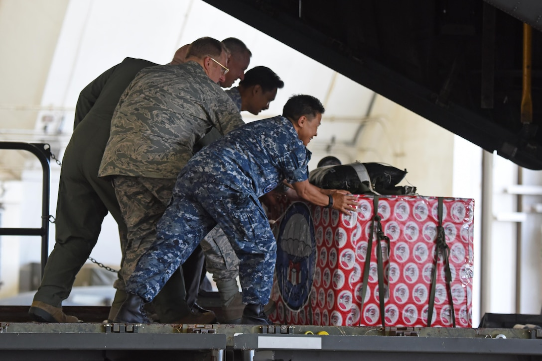 Military and civilian leaders push a box onto a C-130 Hercules during the 2016 Operation Christmas Drop Push Ceremony Dec. 6, 2016, at Andersen Air Force Base, Guam. This year the Japan Air Self-Defense Force, Royal Australian Air Force and U.S. Air Force worked together to continue the tradition of air dropping tools, food, clothing and toys throughout the Pacific. (U.S. Air Force photo/Airman 1st Class Jacob Skovo)