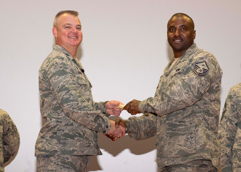 Master Sgt. Kuentin Smart, 46th Aerial Port Squadron, shakes hands with Col. Scott D. Durham, 512th AW commander, during the wing's Community College of the Air Force graduation ceremony, Dec. 3, 2016, Dover Air Force Base, Del. The wing surpassed their goal of awarding 100 CCAF degrees during the year and awarded 109 degrees. (U.S. Air Force Photo/Staff Sgt. Renee Jackson)