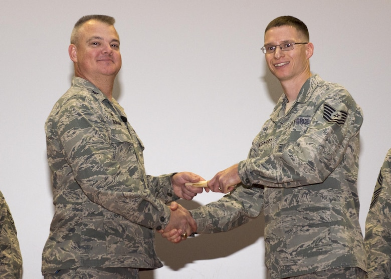 Tech. Sgt. Sean McGahuey, 512th Force Support Squadron, shakes hands with Col. Scott D. Durham, 512th AW commander, during the wing's Community College of the Air Force graduation ceremony, Dec. 3, 2016, Dover Air Force Base, Del. The wing surpassed their goal of awarding 100 CCAF degrees during the year and awarded 109 degrees. (U.S. Air Force Photo/Staff Sgt. Renee Jackson)
