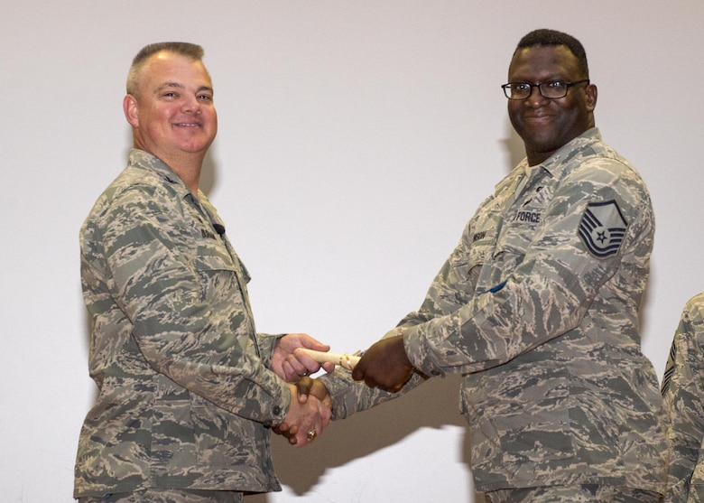 Master Sgt. Darnell Johnson, 512th Aircraft Maintenance Squadron, shakes hands with Col. Scott D. Durham, 512th Airlift Wing commander, during the wing's Community College of the Air Force graduation ceremony Dec. 3, 2016, Dover Air Force Base, Del. The wing surpassed their goal of awarding 100 CCAF degrees during the year and awarded 109 degrees. (U.S. Air Force Photo/Staff Sgt. Renee Jackson)
