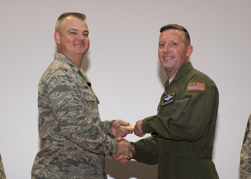 Master Sgt. Scott O'Brien, 709th Airlift Squadron, shakes hands with Col. Scott D. Durham, 512th Airlift Wing commander, during the wing's Community College of the Air Force graduation ceremony, Dec. 3, 2016, Dover Air Force Base, Del. The wing surpassed their goal of awarding 100 CCAF degrees during the year and awarded 109 degrees. (U.S. Air Force Photo/Staff Sgt. Renee Jackson)
