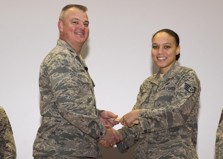 Staff Sgt. Savanna Wesley, 512th Security Forces Squadron, shakes hands with Col. Scott D. Durham, 512th AW commander, during the wing's Community College of the Air Force graduation ceremony, Dec. 3, 2016, Dover Air Force Base, Del. The wing surpassed their goal of awarding 100 CCAF degrees during 2016 and awarded 109 degrees. (U.S. Air Force Photo/Staff Sgt. Renee Jackson)