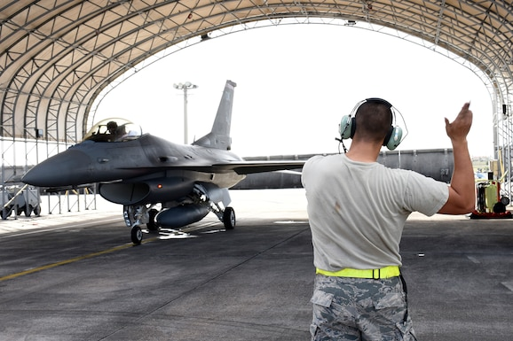 """U.S. Air Force Senior Airman Joshua Utter, a crew chief assigned to the 112th Expeditionary Fighter Squadron, marshals an F-16 Fighting Falcon piloted by Capt. Roy """"Grease"""" Poor during exercise Cope North 2016 on Feb. 15, 2016 at Andersen Air Force Base, Guam. CN16 includes 22 total flying units and nearly 3,000 personnel from six countries and continues the growth of strong, interoperable and beneficial relationships within the Indo-Asia-Pacific region through integration of airborne and land-based command and control assets. (U.S. Air National Guard photo by Staff Sgt. Shane Hughes/Released)"""