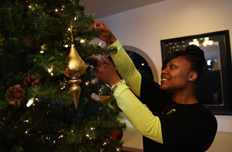 Tech. Sgt. Harriette Oliver, 92nd Logistics Readiness Squadron NCO in charge personal property and passenger travel, hangs ornaments on a tree during the 92nd LRS volunteer event Dec. 2, 2016, at the Spokane Veterans Home in Spokane. Most of the supplies and decorations come from donations, members of staff, families of veterans and volunteers. (U.S. Air Force photo/ Airman 1st Class Sean Campbell)