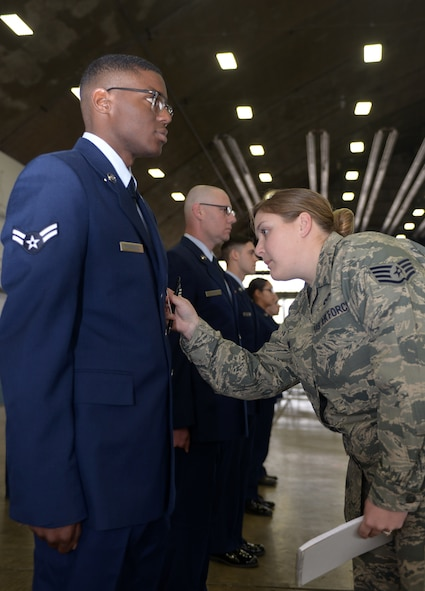 Staff Sgt. Michelle Hoyal, an honor guard flight sergeant assigned to the 28th Force Support Squadron, inspects Airman 1st Class Roger Presswoods' uniform during open ranks in the Pride hangar at Ellsworth Air Force Base, S.D., Dec. 2, 2016. The Ellsworth Honor Guard is responsible for providing military honors throughout a 114,636 square-mile area including South Dakota, western Nebraska and northern Wyoming. (U.S. Air Force photo by Airman 1st Class Donald C. Knechtel)