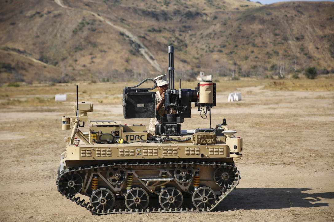 Marine Corps Lance Cpl. Jorge Sainz attaches the M134 Minigun to a robotic vehicle modular system at Camp Pendleton, Calif., June 23, 2016. The Marine Corps Warfighting Laboratory conducted an air-ground integrated experiment to explore new gear for potential use. Sainz is a rifleman assigned to Kilo Company, 3rd Battalion, 5th Marine Regiment. Marine Corps photo by Lance Cpl. Frank Cordoba