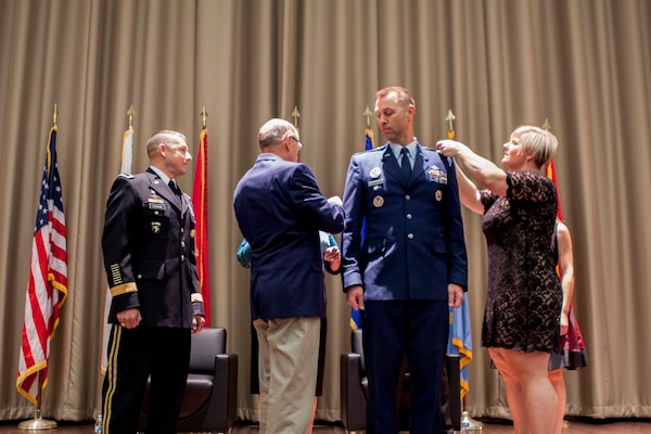 Air Force Lt Col Mike Davis has his new rank of Colonel pinned on by his parents and wife Kristi in a ceremony on Dec. 2.
