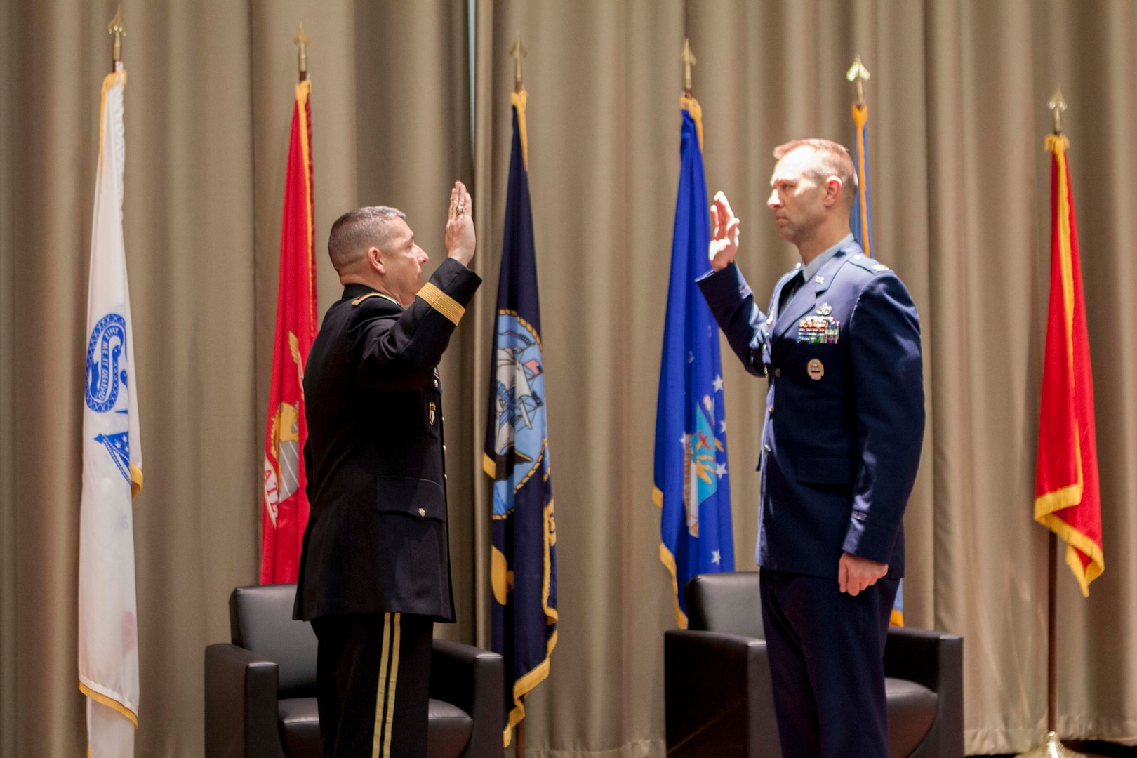 Air Force Lt Col Mike Davis recites the oath of office to DLA Distribution commanding general Army Brig. Gen. John Laskodi as his last action before assuming the rank of Colonel.