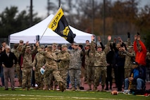 U.S. Army Lt. Col. Yukio Kuniyuki, 344th Military Intelligence Battalion Commander, runs down the sideline with a flag as fellow Soldiers attempt the wave during the Army vs. Navy football game at the Mathis Fitness Center football field on Goodfellow Air Force Base, Texas, Dec. 2, 2016. The Army beat the Navy with a final score of 21 to 7. (U.S. Air Force photo by Senior Airman Devin Boyer/Released)