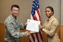 U.S. Air Force Lt. Col. Donald Yu, 17th Training Group Acting Commander, presents the 316th Training Squadron Student of the Month award for November 2016 to U.S. Marine Corps Lance Cpl.  Shala Buie at Brandenburg Hall on Goodfellow Air Force Base, Texas, Dec. 2, 2016. (U.S. Air Force photo by Airman 1st Class Chase Sousa/Released)