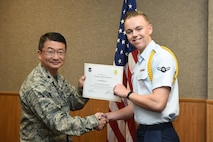 U.S. Air Force Lt. Col. Donald Yu, 17th Training Group Acting Commander, presents the 312th Training Squadron Student of the Month award for November 2016 to Airman Seth Williams at Brandenburg Hall on Goodfellow Air Force Base, Texas, Dec. 2, 2016. (U.S. Air Force photo by Airman 1st Class Chase Sousa/Released)