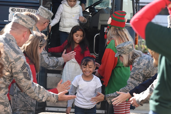 Children from local communities are greeted by Team V members during the 58th annual Operations Kids Christmas, Dec. 2, 2016, Vandenberg Air Force Base, Calif. Since its inception in the 1950s, OKC has been an opportunity for uniformed members to give back to the community and provide children a day full of games, gifts, and recreational activities. (U.S. Air Force photo by Senior Airman Robert J. Volio/Released)