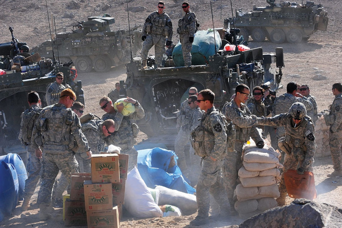 U.S. Soldiers transport and unpack humanitarian aid to an Afghani town.