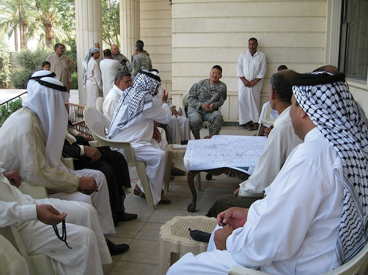 A U.S. Army infantry officer trained in Arabic negotiates with Iraqi tribal leaders. Iraq's political landscape is particularly challenging in part due to tribal influences.