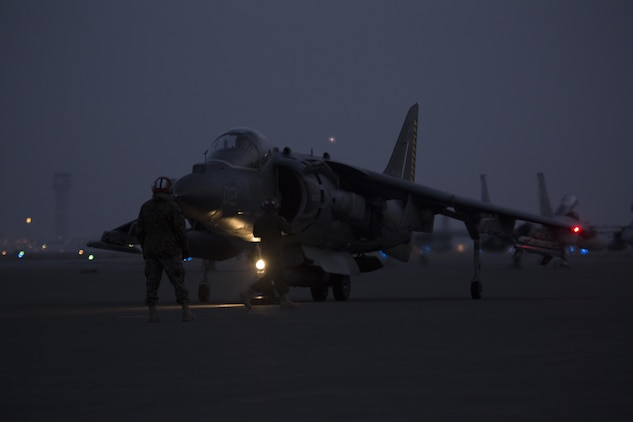 U.S. Marines with Marine Attack Squadron (VMA) 542 guide a U.S. Marine Corps AV-8B Harrier on the flight line after its arrival to Chitose Air Base, Japan, Dec. 5, 2016. Following the arrival of the squadron's Harriers, a press conference was held to acknowledge questions pertaining to the aircraft and the Aviation Training Relocation Program. (U.S. Marine Corps photo by Lance Cpl. Joseph Abrego)