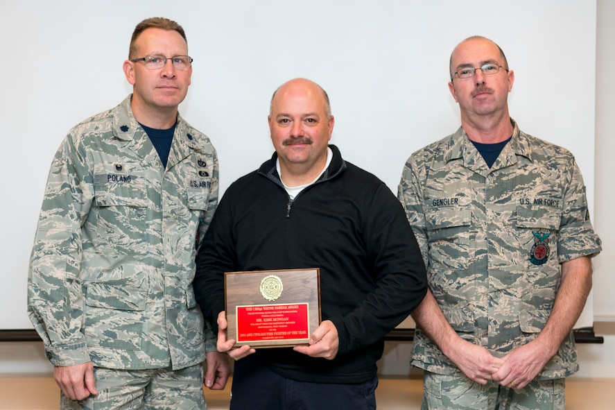 Lt. Col. John Poland (left), the civil engineering squadron commander at the 167th Airlift Wing in Martinsburg, W.Va., and Chief Master Sgt. Jeffery Gengler (right), fire chief at the 167th, recognize Kirk Mongan (middle), assistant chief of operations at the 167th AW Fire Emergency Services, as 2015 Air National Guard Civilian Firefighter of the Year, Dec. 2, 2016. Mongan was chosen from all of the civilian Air National Guard Firefighters by the Air National Guard Fire Chiefs Association. (Air National Guard photo by Staff Sgt. Jodie Witmer)