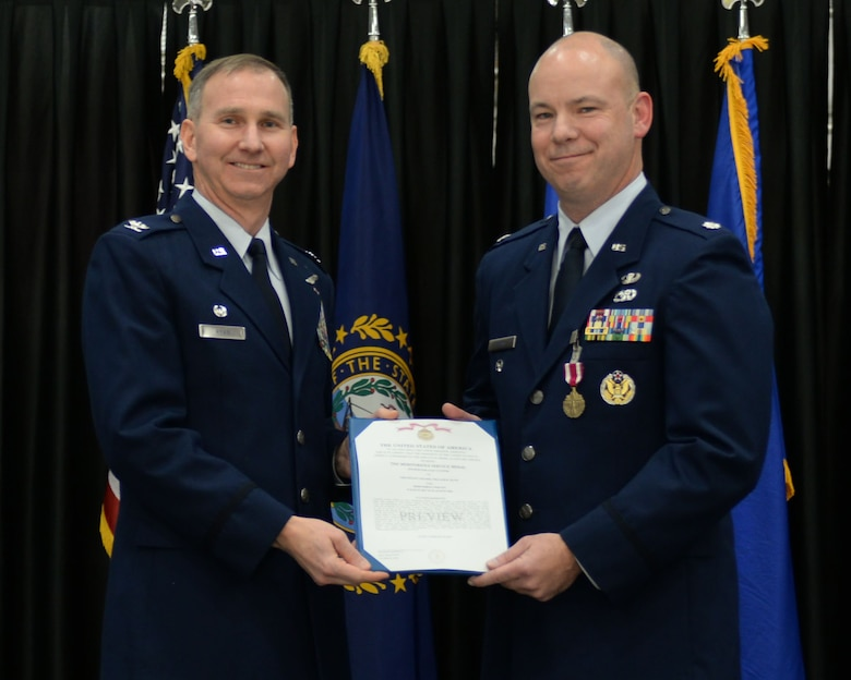 Lt. Col. William Davis, right, 157th Air Refueling Wing vice commander, is presented the Meritorious Service medal and certificate by Col. James Ryan, 157 ARW commander, during a promotion ceremony at Pease Air National Guard Base, N.H., Dec. 3, 2016. During the ceremony, Davis was promoted to colonel. (U.S. Air National Guard photo by Staff Sgt. Kayla Rorick)