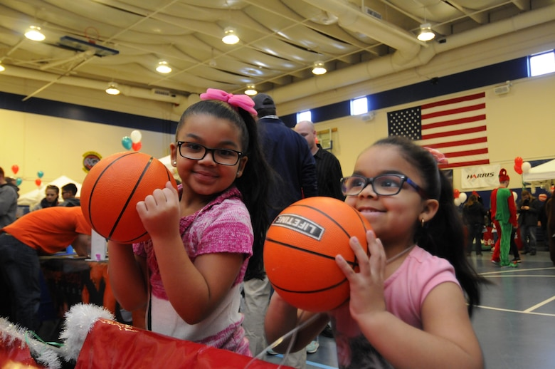 Ariana and Liana Zayas shoot hoops during the 2016 Candy Land Children's Holiday Fest at Schriever Air Force Base, Colorado, Saturday, Dec. 3, 2016. The basketball game was one of several interactive booths for families to find information and play games. (U.S. Air Force photo/1st Lt. Darren Domingo)