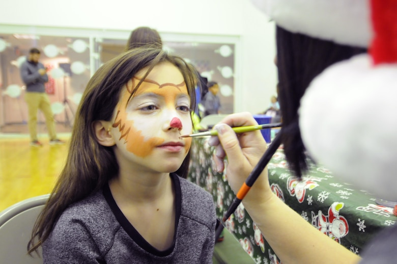 A face-painter transforms Aspen Fletcher into a tiger during the 2016 Candy Land Children's Holiday Fest at Schriever Air Force Base, Colorado, Saturday, Dec. 3, 2016. After face painting, children could walk next door to enjoy free lunch or meet Santa. (U.S. Air Force photo/1st Lt. Darren Domingo)