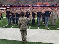 Lt. Col. Yira Muse, 313th Recruiting Squadron commander, swears in members of the squadron's Delayed Entry Program during the Syracuse vs. North Carolina  States football game at Syracuse University, New York, Nov. 12. Standing in formation with their DEP members are Staff Sgt. Simon Martin and Staff Sgt. Kevin Dunham, 313th RCS E-flight.