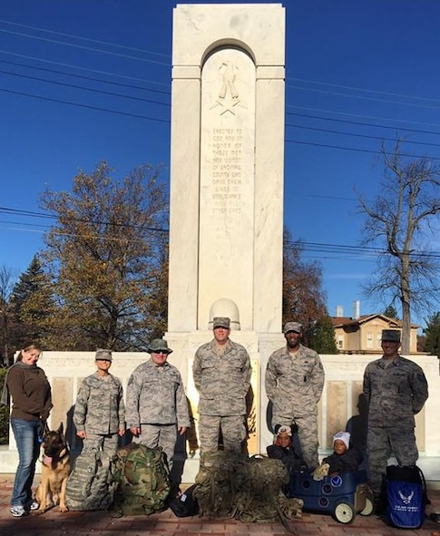 Members of the 339th Recruiting Squadron pose for a photo in front of the World War II Monument during the Saginaw County Veterans Memorial Plaza 5K run/walk at Hoyt Veterans Memorial Park in Michigan, Nov. 12. From left are: Stephanie Graham, German Shephard Roman, Tech. Sgt. Jessica Welch, Master Sgt. Gregory Lamb, Senior Master Sgt. Dale Graham, Tech. Sgt. Henry Edwards III, sons Jaxon and Aiden, and Tech. Sgt. Joseph Glorso.
