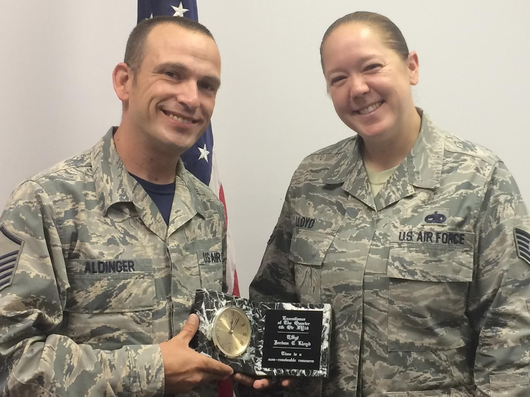 Master Sgt. Timothy Aldinger, 368th Recruiting Squadron flight chief, presents Tech. Sgt. Jordan Lloyd with the flight's 4th Quarter Executioner award in Taylorsville, Utah, Oct. 14. Lloyd was able to process 11 applicants in seven weeks before attending Non-Commissioned Officer Academy at Peterson Air Force Base in Colorado.