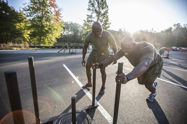 An FFI student executes a forward sled push as a part of the finisher for the day's workout while being motivated by another student.